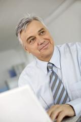 Portrait of senior businessman in office working on laptop