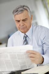 Senior businessman reading newspaper with puzzled look