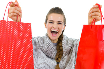 Happy woman in sweater showing red shopping bags