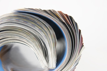 Rolled up magazine pages close-up over white background