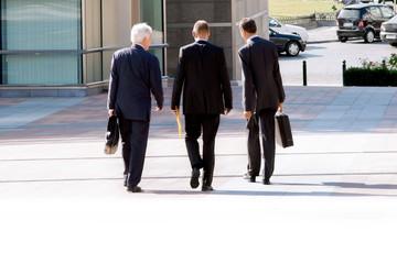 Three businessmen walking on the street.