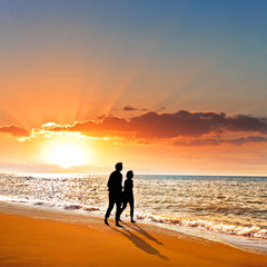 Young couple walking on the beach at sunset.