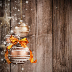Christmas theme with golden glass balls on blur wooden texture