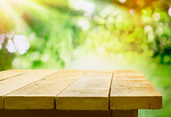 Empty wooden table with garden bokeh
