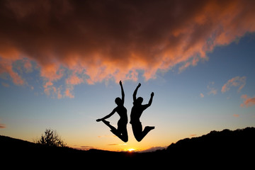 silhouette of couple jumping in sunset