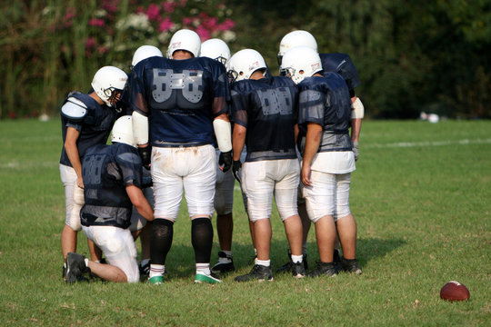 Pro American Football Players Huddle