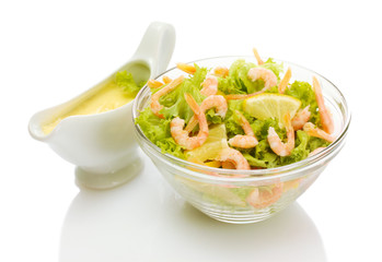 salad with shrimps, lemon and lettuce leaves in bowl and sauce,