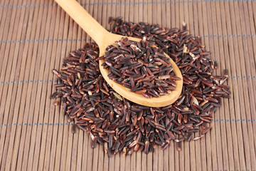 black rice  in wooden  spoon on bamboo mat