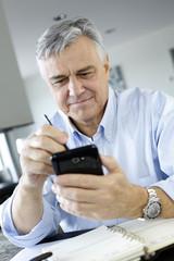 Portrait of senior businessman using smartphone