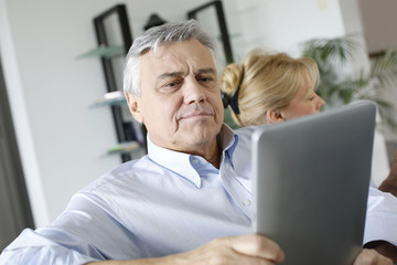 Senior man reading news on tablet sitting in couch