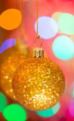 Golden christmas ball on bokeh background