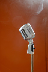 Vintage microphone against brown background.