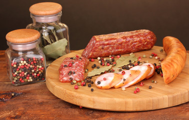 Tasty sausages on chopping board on browm background