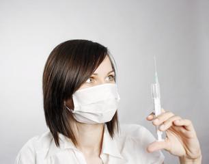 Nurse in mask with syringe