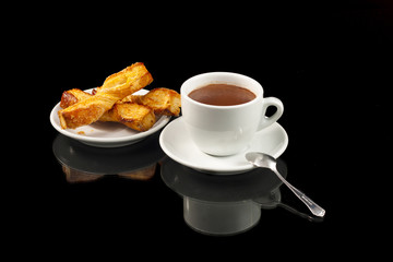 a cup of chocolate with puff ties, isolated on black