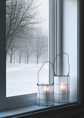 Cozy lanterns and winter landscape seen through the window