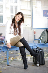 Fröhliche junge Frau wartet auf den Bus