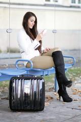 Junge Frau wartet auf den Bus und schaut auf ihr Handy