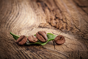 Coffee grains and green leaf on grunge wooden background