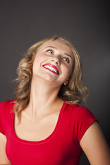 Blonde laughs in a studio. Wonderful smile, red pomade