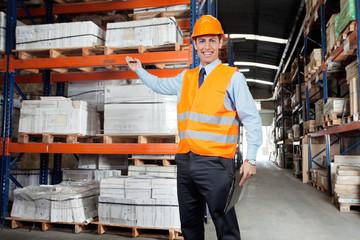 Confident Supervisor Showing Stock On Shelves