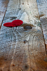 Red heart shaped rose petal on rustic wooden table