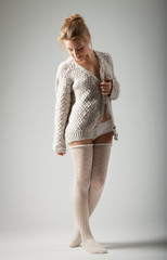 beautiful young woman in knitted jumper  on gray background