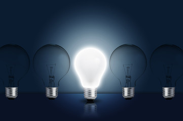 Incandescent light bulb in a row with middle one on