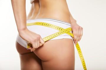 Girl in white underwear measuring her body
