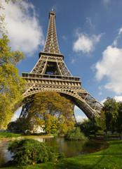 sunlit Eiffel Tower, Paris, over park and lake
