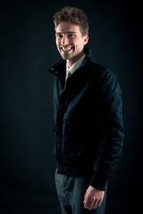 Portrait of handsome, smiling man against dark background.
