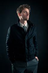 Portrait of handsome, confident man against dark background.