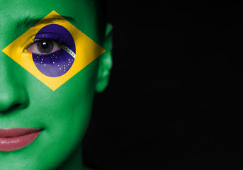 Portrait of a woman with the flag of the Brazil on face