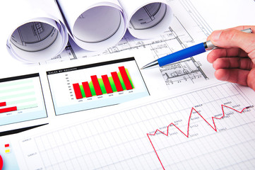 hand points to the growth charts on financial documents