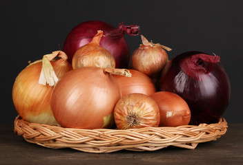 Ripe onions on wicker cradle on wooden table on black
