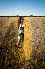 Brunette girl portrait and straw bale
