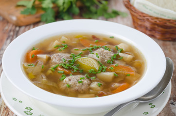 Plate of vegetable soup with meatballs on the wooden table close