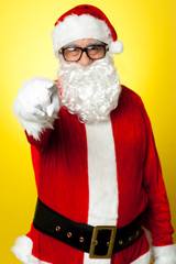 Jelly-belly Santa in spectacles pointing at you