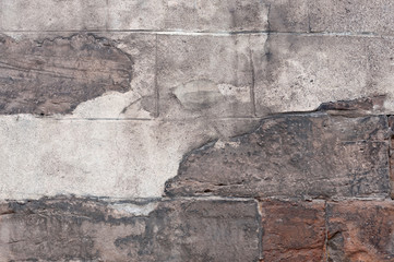 Old stone wall with peeling plaster.
