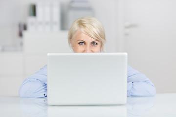 frau im büro schaut über laptop