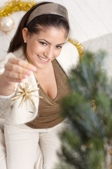Happy woman decorating christmas tree