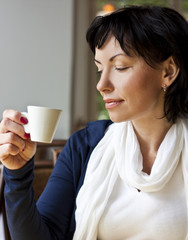 Сute woman looking away with cup of coffe
