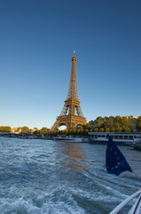 Eiffel Tower, Paris, at sunset as seen from Seine with EU banner