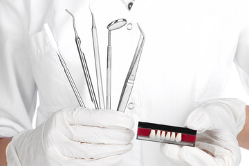 Set of dental tools and denture in dentists hands