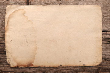Weathered old paper on a wooden background