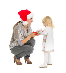 Happy mother making Christmas present to baby girl