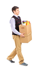 Smiling male walking with boxes, moving into a new home