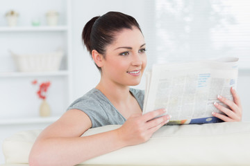 Smiling woman sitting on the couch and reading newspaper