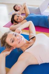 Smiling women doing sit ups