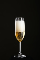 Glass of champagne on a black background.